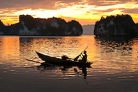 Raja Ampat Archipelago, West Papua, Indonesia, December 2010. Women are fishing for shrimp at sunrise. Thousands of small islands fringed by coral reefs and blue water mangroves litter the Raja Ampat archipelago. The turquoise and blue waters are teeming with marine life that forms the livelihood for the local Papuan population. The Raja Ampat Research & Conservation Centre (RARCC) supports the locals to develop a community based, sustainable tourism project, inviting visitors to explore their islands by sea kayak and experience the culture by staying amongst the local people in traditional style homestays. Photo by Frits Meyst/Adventure4ever.com