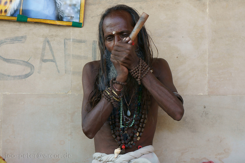 Sadhu smoking Ganja as his worshipped god  Shiva at the river Ganga in Varanasi, India.