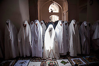 A group of women, dressed in white chadors, during friday prayers. Traditionally, in the region, white is worn to ward off evil.