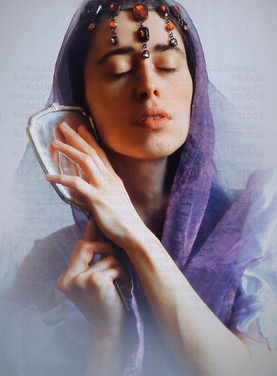 A woman in a violet veil and a ruby oriental  headdress, with closed eyes and a dreamy facial expression, holding a mirror.