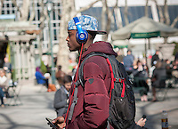A visitor to Bryant Park wears his Beats by Dr. Dre headphones as he walks through the park in New York on Friday, March 21, 2014. Friday was the first full day of Spring heralding in balmy weather for the first half of the weekend. Sunday, the temperature will drop back into the 40's. (© Richard B. Levine)