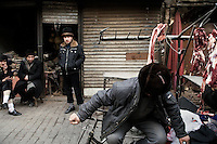 Uighur men stand near a butcher stand in Kashgar, Xinjiang, China.
