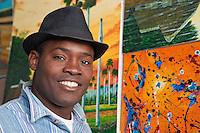 Cuba, Havana.  Afro-Cuban Vendor Selling Paintings in Handicrafts Market.