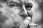 Close up of a man, smoking a cigerette with dirt in his fingernails, surrounded by smoke