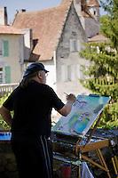 Artist painting town of Bourdeilles popular tourist destination near Brantome in Northern Dordogne, France