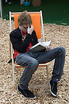 A young festival goer listening to his ipod music centre, and reading a good book at the same time. The Hay Festival, Hay on Wye, Powys, Wales, Great Britain. 2006.