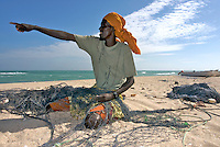 A fisherman points out to the Indian Ocean while mending nets in the coastal village of Eyl. The town is a base for local pirates, and piracy has fuelled the local economy.