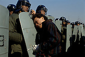 Kuro gu, South Korea<br /> December 18, 1987<br /> <br /> A mother is separated from her arrested son by a wall of government police after a battle with students at a nearby polling station. The students claim that the polling station had been the filled with fraudulent votes.<br /> <br /> After two decades of building an economic miracle, in the summer of 1987 tens of thousands of frustrated South Korean students took to the streets demanding democratic reform. &quot;People Power&quot; Korean-style saw Koreans from all social spectrums join in the protests.<br /> <br /> With the Olympics to be held in South Korea in 1988, President Chun Doo Hwan decided on no political reforms and to choose the ruling party chairman, Roh Tae Woo, as his heir. The protests multiplied and after 3 weeks Chun conceded releasing oppositionist Kim Dae Jung from his 55th house arrest and shaking hands with opposition leader Kim Young Sam. Days later he endorsed presidential elections and an amnesty for nearly 3,000 political prisoners. It marked the first genuine initiative of democratic reform in South Korea and the people had their victory.