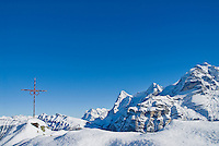 Summit cross on small mountain peak with view of mountains in background, Gimmelwald, Switzerland