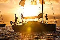 A man playing guitar and woman standing on bow of yacht at sunrise in lagoon off Tahaa Island
