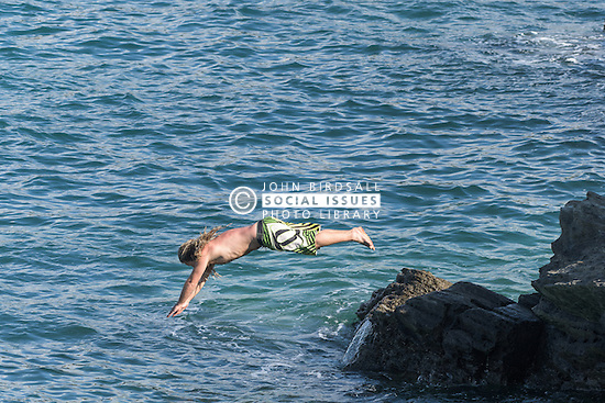 A holidaymaker dives into the sea off rocks on The headland in Newquay, Cornwall.