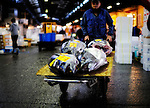 A market worker pushes a cart of blue fin tuna through a section of the world's largest fish and marine products market in Tsukiji, Tokyo on Monday 30 March 2009.