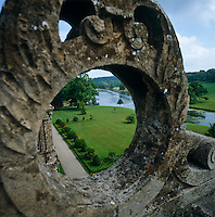 View through a stone carving on the roof at Longleat down to the gardens and the river