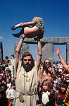 Bev Richardson or Pagan Bev. 1970's style hippies attend the second free festival at Stonehenge to celebrate the summer solstice June 21st 1975. This boy has just been baptised.