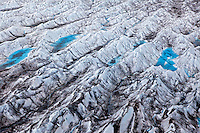 Aerial view of crevasse patterns and melt water ponds on Kinik Glacier, Alaska, USA