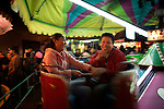A Mexican couple play in a merry-go-round outside the Virgin of Carmen church in Toluca City, some 70 km from Mexico City, July 16, 2007. Photo by Javier Rodriguez