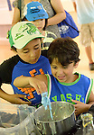 Seaford, New York, U.S. 20th July 2013. TRISTAN BISSOONDIAL, 5, is holding blue slime he made, and his brother TYLER BISSOONDIAL, 8,  is looking on, during Science Exploration Moon Day, presented by Long Island Fringe Festival 5. There were many science projects and activities at the Tackapuahsa Museum and Preserve, the host of this family event.