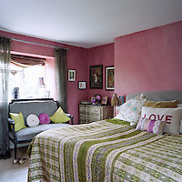 In the master bedroom the walls have been distempered a powdery strawberry-pink and the bed is dressed in contrasting green checks