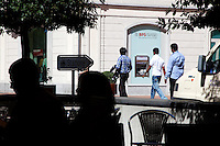 Switzerland. Canton Ticino. Chiasso. Banca Popolare di Sondrio (Suisse). Three men walked on the main street. They are economic migrants and have asked for political asylums in Switzerland. A couple sits in the shadow at the Mövenpick restaurant and eats his lunch. 08.04.11 © 2011 Didier Ruef