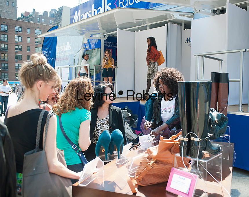 """An employee promotes products during Marshalls Fabulous Found Fashion Tour promotional event by Marshalls Department Store in Union Square in New York on Thursday, September 13, 2012. The tour featuring a fashion show and a """"guess the price game"""" was to promote the stores fall designer apparel. (© Richard B. Levine)"""