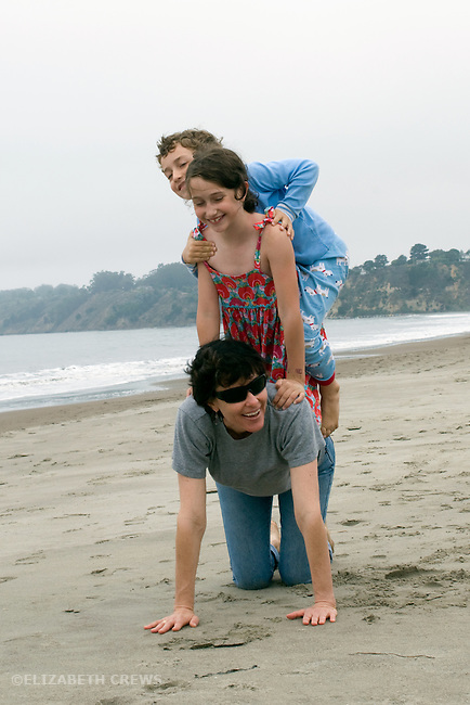 Stinson Beach, CA Aunt and niece, eight, and nephew, six, performing acrobatic tricks during beach vacation  MR