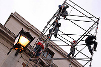 Operai edili montano una impalcatura per il restauro di un palazzo..Construction workers mount a scaffolding for the renovation of a building.....