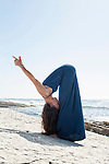Woman in goddess yoga forward bend pose near the sea.