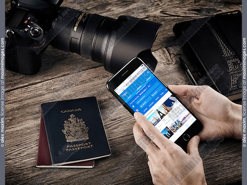 Woman hands with Apple iPhone 7 displaying flight information on a table with passports, a camera and a notebook, traveling conceptual still life