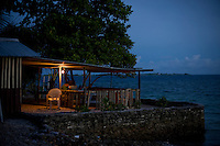 A lagoon-side cafe in Jabor, Jaluit Atoll, serves coffee and offers a place to sit. In places with high population densities, people build into the lagoon, using sea walls to protect against the waves. In the face of increasing tropical storms and sea level rise, these sea walls prove ineffective.