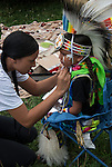 Native American , Chaske Hill Sicangu Lakota and Seneca , mother dressing and preparating her 3 year old son for pow wow dance contest at the Thunderbird powwow in Queens, NY .