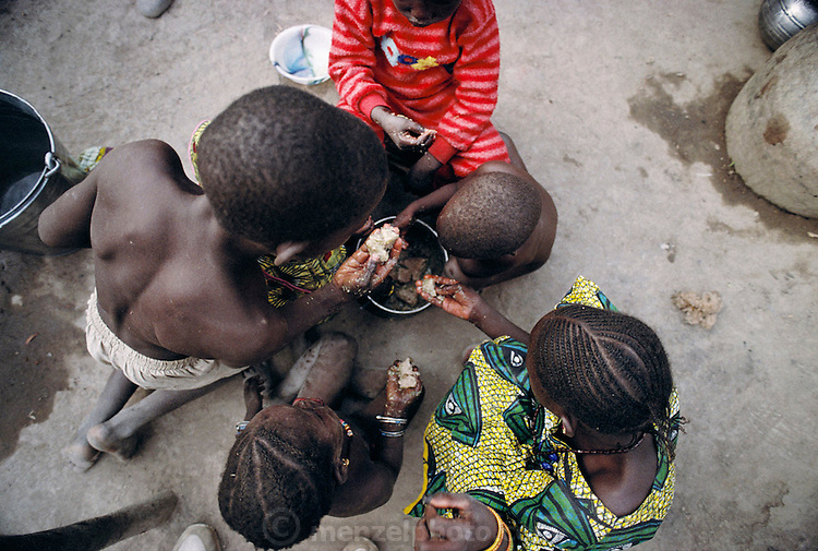 Members of the Natomo family eat their communal dinner of fish and rice. In the village of Kouakourou, Mali, on the banks of the Niger River. The Natomo family lives in two mud brick houses in the village of Kouakourou, Mali, on the banks of the Niger River. They are grain traders and own a mango orchard. According to tradition Soumana is allowed to take up to four wives; he has two. Wives Pama and Fatoumata are partners in the family and care for their many children together. Material World Project.