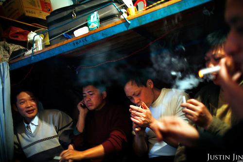 "Jeans workers smoke in their dormitory at Mr Yang's factory in Zhongshan city, China. .This picture is part of a photo and text story on blue jeans production in China by Justin Jin. .China, the ""factory of the world"", is now also the major producer for blue jeans. To meet production demand, thousands of workers sweat through the night scrubbing, spraying and tearing trousers to create their rugged look. .At dawn, workers bundle the garment off to another factory for packaging and shipping around the world..The workers are among the 200 million migrant labourers criss-crossing China.looking for a better life, at the same time building their country into a.mighty industrial power."