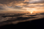 Kauehi Atoll, Tuamotu Archipelago, French Polynesia; a sunset sky reflects on the water's surface after a dive