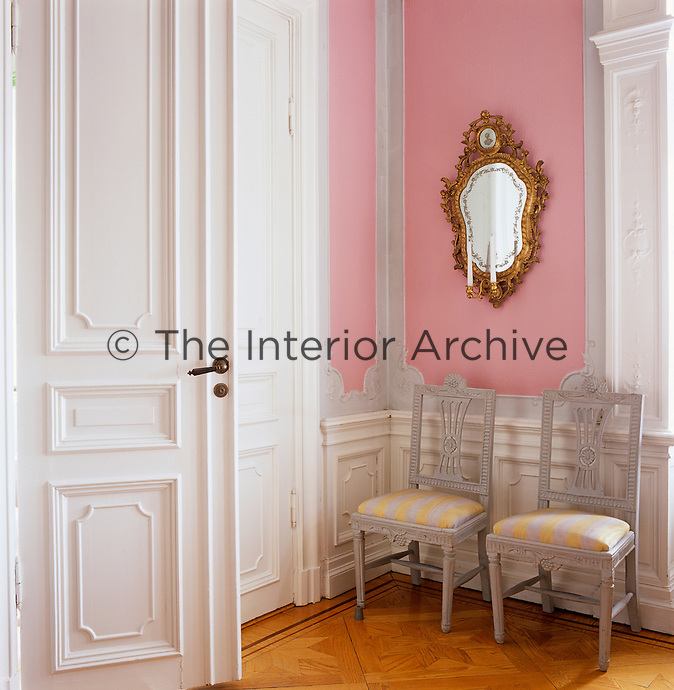 An elaborate gilt-framed mirror hangs on the pink wall of this drawing room with a pair of 18th century Scandinavian dining chairs
