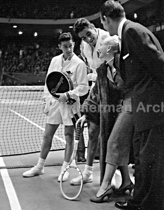 Hollywood film star Ginger Rogers spins racket for match between (Lto R) Ken Rosewall and Pancho Gonzales at Madison Square Garden, February 1957. Jack Kramer on Right. Photograph by John G. Zimmerman.