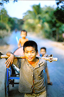 We rented a motorbike and explored some of the rural villages nearby. This group of children were wheeling a water barrel from the water well, back home. Cambodia. Pentax Spotmatic. 2004