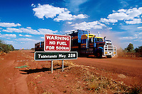 "A large road train passes a road sign warning ""no FUEL FOR 500KM"" on the Tablelands highway, Northern Territory , Australia"