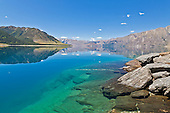 A sunny day illuminates the blue and green hues of Lake Hawea, Central Otago, New Zealand.