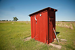 Red outhouse behind an old one-room schoolhouse, Okla.