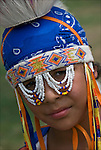 Head and shoulder portrait of young Native American boy dressed in pow wow rRegalia. Examples of ethnic pride, heritage, celebration, and traditional folk art crafts.