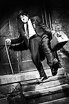 Man in a black suit with a bag Charlie Chaplin mime tripping and falling from a staircase. Artistic performance humorous concept. Performing artist Peter Jarvis. Toronto Canada.