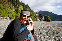 Stephanie Haynes makes a cell phone call from the beach before hiking on the Saddle and Alpine Ridge trail in Kachemak Bay State Park, near Homer, Alaska.