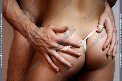 Closeup of a couple. Man with his hands on woman's buttocks.