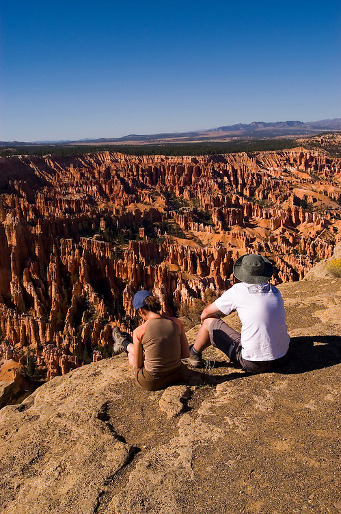 Couple relaxing at Bryce Canyon National Park, Ampitheater and Hoodoos of Silent City from Bryce Point, dawn, erosion, arid, Utah, UT, Southwest America, American Southwest, US, United States, tourists, travelers, sightseeing, no model release, Image ut343-18171, Photo copyright: Lee Foster, www.fostertravel.com, lee@fostertravel.com, 510-549-2202