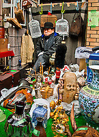 Japanese vender in bowler hat selling antiques at the famous Setagaya Boro-ichi market which is 400 years old & held only twice a year.