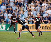 Andy Najar (14) of D.C. United goes is fouled on a header by Neven Markovic (25) of Sporting Kansas City during the game at Livestrong Sporting Park in Kansas City, Kansas.  D.C. United lost to Sporting Kansas City, 1-0.