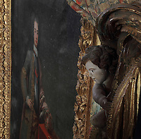 Sculpted angel and portrait of King John V or Joao V of Portugal, 1689-1750, by Domenico Dupra, 1725, in the Black Room of the Joanina Library, or Biblioteca Joanina, a Baroque library built 1717-28 by Gaspar Ferreira, part of the University of Coimbra General Library, in Coimbra, Portugal. The Casa da Livraria was built during the reign of King John V or Joao V, and consists of the Green Room, Red Room and Black Room, with 250,000 books dating from the 16th - 18th centuries. The library is part of the Faculty of Law and the University is housed in the buildings of the Royal Palace of Coimbra. The building is classified as a national monument and UNESCO World Heritage Site. Picture by Manuel Cohen