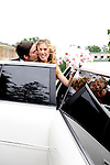 Newly weds enter their white limo and embrace