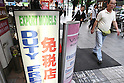 July 1, 2010 - Tokyo, Japan - A pedestrians walks past a sign written in Chinese displayed at an electronics store in Akihabara district, Tokyo, Japan, on July 1, 2010. On Tursday, Japan will significantly relax visa requirements for Chinese citizens to attract an increasing number of big-spending Chinese tourists to boost its economy. Japanese Foreign Minister Katsuya Okada told a press conference earlier that the number of households eligible to visit will increase 10-fold to 16 million a year.