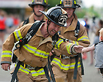 Eagle fire department member Nick Piccono reaches out to a young spectator, as he runs in full fire fighting gear in the First Responders Team Challenge during the Main Street Mile sponsored by Saint Alphonsus in downtown Boise, Idaho on June 22, 2012.